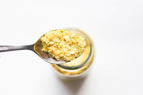 Spoon of vegan nutritional yeast flakes on white background